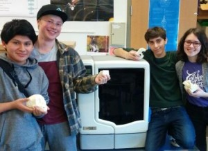 Engineering students holding various objects made with the 3D printer